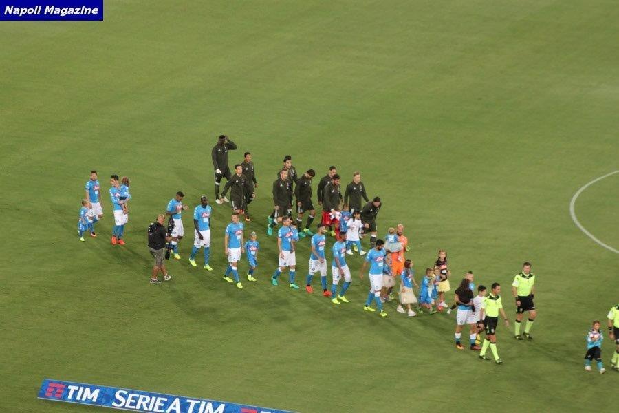 Sofia De fenza e Michele Tridenti rispettivamente mano a mano con Riccardo Montolivo e Marek Hamsik e le squadre che scendono in campo.