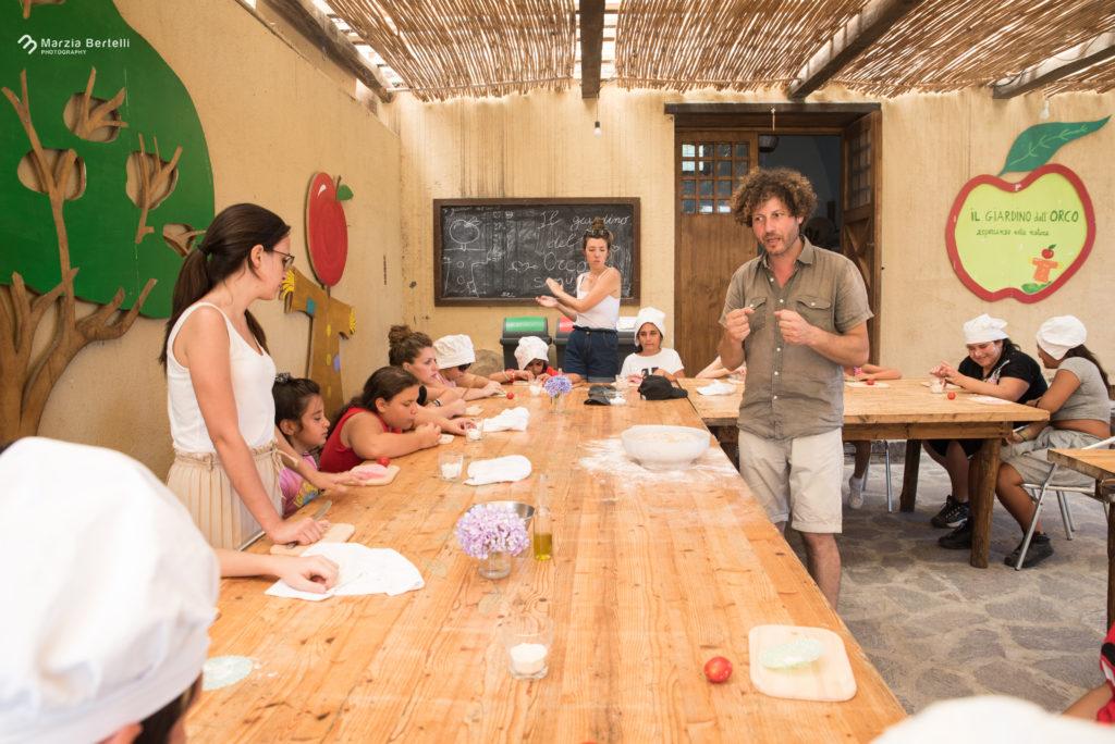 Presso il giardino dell'Orco, foto alla tavolata di bambini intenti a realizzare il proprio impasto della pizza, mani sporche di farina e cappellini da chef in testa. Operatori affianco ai ragazzi in foto.