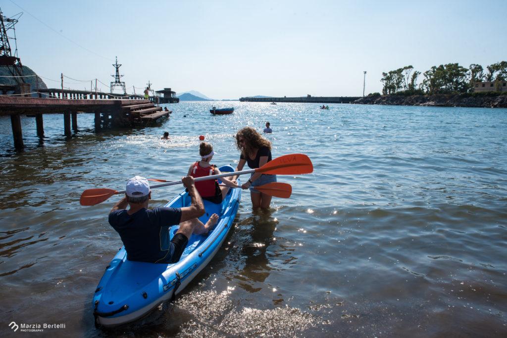 Presso Ilva, foto ad una canoa presa di spalle, sopra un operatore dell'Ilva e nel posto anteriore una nostra bambina con pagaia in mano e una nostra operatrice che l'aiuta.