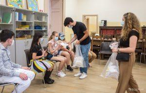 Distribuzione di un piccolo regalo ai nostri bambini, un cappellino bianco con i loghi dell'UICI della Fondazione strachan Rodinò e della Delta Ceramica.