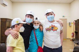 """""""Un piccolo gruppo di tre bambini ed un operatore si lasciano fotografare insieme, sorridenti e con i cappellini sulla testa"""